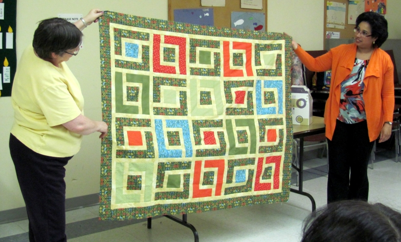 Anja (r), here  displaying the quilt she made for last year's Lunch Box Challenge, is the recipient of this year's Kathy Ogden Memorial Scholarship.