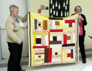 Ellen (R) made this quilt for Jean E, who was unable to make the meeting, but Helen helps show off the quilt.